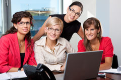 Team of businesswomen. Team of young businesswomen using laptop computer in meeting room. Looking at camera, smiling royalty free stock photos