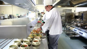 Team of busy chefs working at the order station stock footage