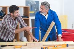 Team carpenters comparing work pieces. Team of carpenters comparing work pieces Stock Images