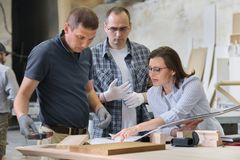 Team of carpenters workshop workers discussing a furniture project with client, designer, engineer stock photos