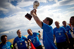 Team celebration,  Winners of Monster Music Festival Beach Soccer tournament. Peugeot beach soccer team celebrating with a cup at Pärnu beach, Estonia Royalty Free Stock Photo