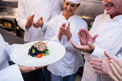 Team of chefs applauding. In the kitchen royalty free stock image