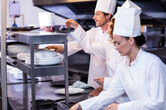 Team of chefs arranging plates on the order station. In the kitchen Royalty Free Stock Images