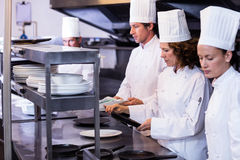 Team of chefs arranging plates on the order station. In the kitchen Royalty Free Stock Image