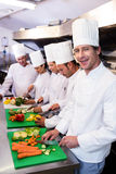 Team of chefs chopping vegetables. On the chopping board Stock Photo