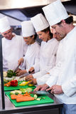 Team of chefs chopping vegetables. On the chopping board in the kitchen Royalty Free Stock Photos