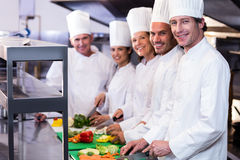 Team of chefs chopping vegetables. Team of chefs smiling at camera while chopping vegetables on the chopping board in the kitchen Stock Photo