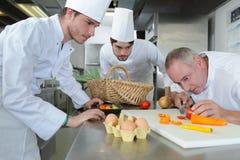 Team chefs and cooks in restaurant kitchen. Team of chefs and cooks in restaurant kitchen Stock Photo
