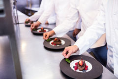 Team of chefs finishing dessert plates in the kitchen Royalty Free Stock Images