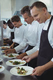 Team of chefs garnishing meal on counter Royalty Free Stock Photo