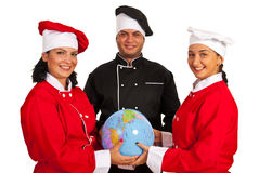 Team of chefs holding world globe. Team of three chefs holding world globe and standing together isolated on white background Royalty Free Stock Image