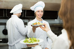 Team of chefs at kitchen. Team of positive chefs and young waiter at the restaurant kitchen Stock Photos