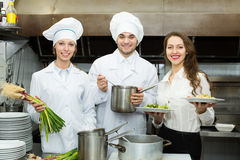 Team of chefs at kitchen. Team of positive chefs and young waiter in the restaurant kitchen Royalty Free Stock Image