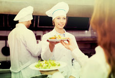 Team of chefs at kitchen. Team of positive chefs and young waiter at the restaurant kitchen Stock Photo