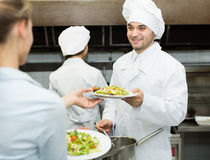 Team of chefs at kitchen. Team of chefs and young waiter at the restaurant kitchen Royalty Free Stock Image