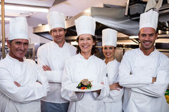 Team of chefs with one presenting a dish. Team of chefs in the kitchen with one presenting a dish Royalty Free Stock Photos