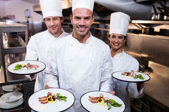 Team of chefs presenting their dishes. Portrait of chefs presenting their dishes in the kitchen Royalty Free Stock Image