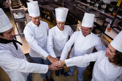 Team of chefs putting hands together. And smiling in a commercial kitchen Royalty Free Stock Photography