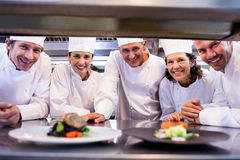 Team of chefs smiling at camera. In the kitchen Royalty Free Stock Photos