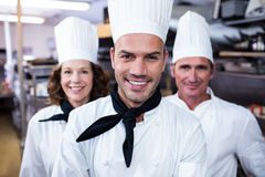 Team of chefs smiling in commercial kitchen. Portrait of happy chefs team standing together in commercial kitchen Stock Image