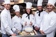 Team of chefs smiling in commercial kitchen. Portrait of happy chefs team standing together in commercial kitchen Stock Photo