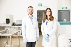 Team of chemists ready to run some tests. Two good looking chemists standing in the middle of a laboratory, ready for work Royalty Free Stock Photos