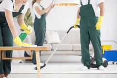 Team of cleaners cleaning room. A team of cleaners in the green overalls cleaning a room by vacuuming and dusting royalty free stock images