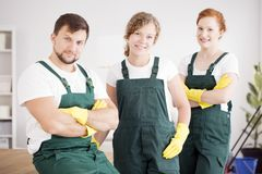 Team of cleaners. In green overalls and yellow gloves royalty free stock photos