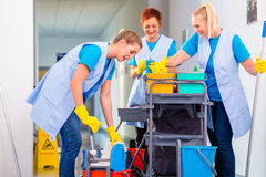 Team of cleaning ladies working. Commercial cleaning brigade working in corridor stock photography