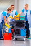 Team of cleaning ladies working. Commercial cleaning brigade working in corridor royalty free stock photography