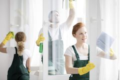 Team cleaning office windows. Team of workers cleaning white office windows wearing yellow gloves and protective clothing royalty free stock photography