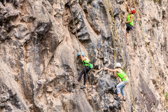 Team Of Climbers Climbing un mur de roche photos stock