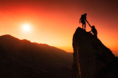 Team of climbers help to conquer the summit. In teamwork in a fantastic mountain landscape at sunset Royalty Free Stock Photo