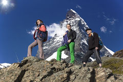 Team of climbers walks against alpine background Stock Photos