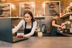 Team of coffee shop workers working near the counter with laptop computer and making coffee, cafe business stock photography