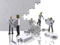 A team collaborating to build a puzzle Royalty Free Stock Photo