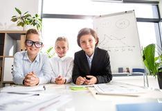 Cheerful kids are expressing gladness. Team collaboration concept. Portrait of smiling satisfied happy children are sitting at desk with papers in light office stock photo