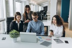 Team of colleagues brainstorming together while working on the computer. To royalty free stock image