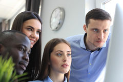 Team of colleagues brainstorming together while working on the computer. Royalty Free Stock Photo