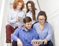 Team con il computer del pc della compressa che si siede sulla scala Immagini Stock Libere da Diritti
