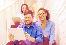 Team con il computer del pc della compressa che si siede sulla scala Fotografia Stock Libera da Diritti