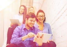 Team con il computer del pc della compressa che si siede sulla scala Immagini Stock