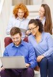 Team con il pc della compressa e del computer portatile sulla scala Fotografia Stock