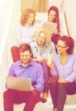 Team con il pc della compressa e del computer portatile sulla scala Fotografie Stock