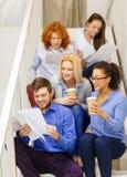 Team con le carte e porti via il caffè sulla scala Fotografia Stock Libera da Diritti