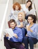 Team con le carte e porti via il caffè sulla scala Fotografia Stock