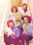 Team con le carte e porti via il caffè sulla scala Immagine Stock Libera da Diritti