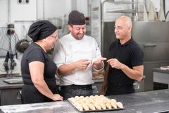 Team of Confectioners talking about the croissant recipe stock images