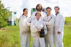 Team Of Confident Beekeepers At-Bienenhaus Lizenzfreie Stockfotos