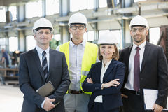 Team of confident business people wearing hardhats in metal industry Royalty Free Stock Photos